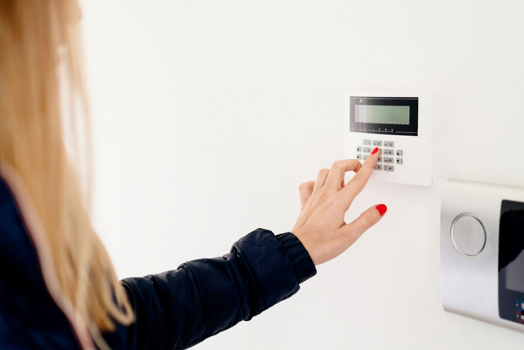 Person using touch pad for their smart home alarm system
